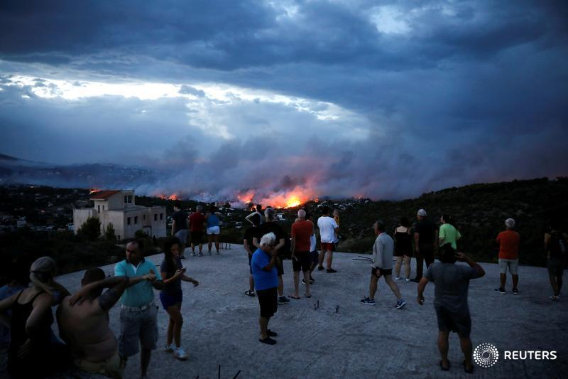 People watch a wildfire burning in the town of Rafina