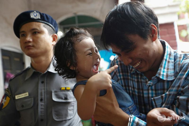 Detained Reuters journalist Kyaw Soe Oo plays with his daughter as he is escorted by police at Insein court in Yangon, Myanmar