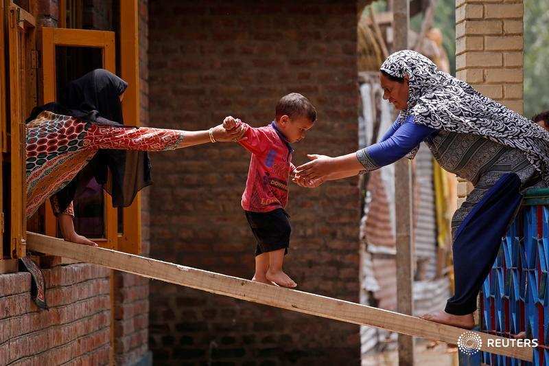 Women help a child to cross over to another house on a wooden plank after flash floods on the outskirts of Srinagar