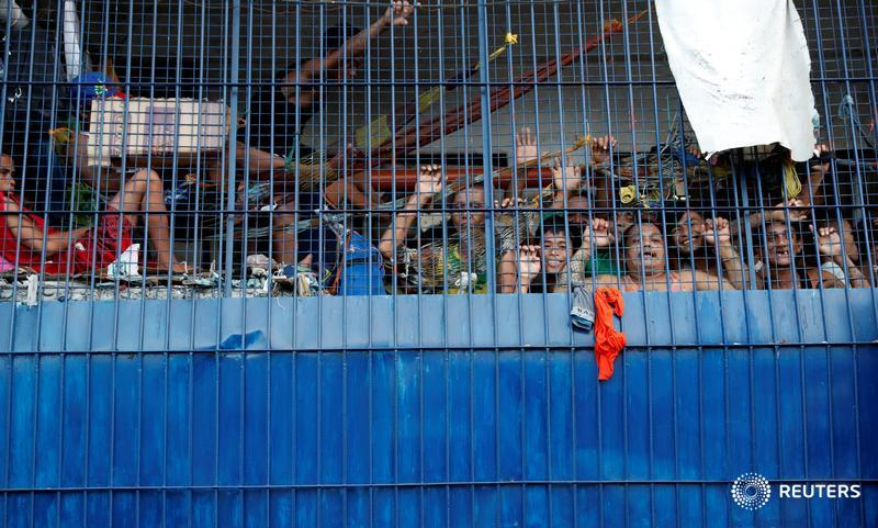 Detainees look out from a cell at a police station in the Philippines