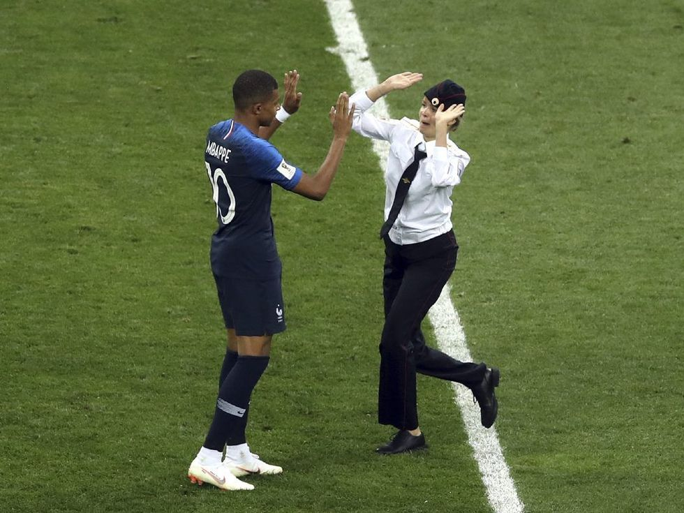 Iconic image from #WorldCupFinal France's @KMbappe high-fives a @pussyrrriot member after she invaded the pitch to protest political oppression in Russia. Photo: @TStavrak / @AP https://t.co/SfLdzUSlIL
