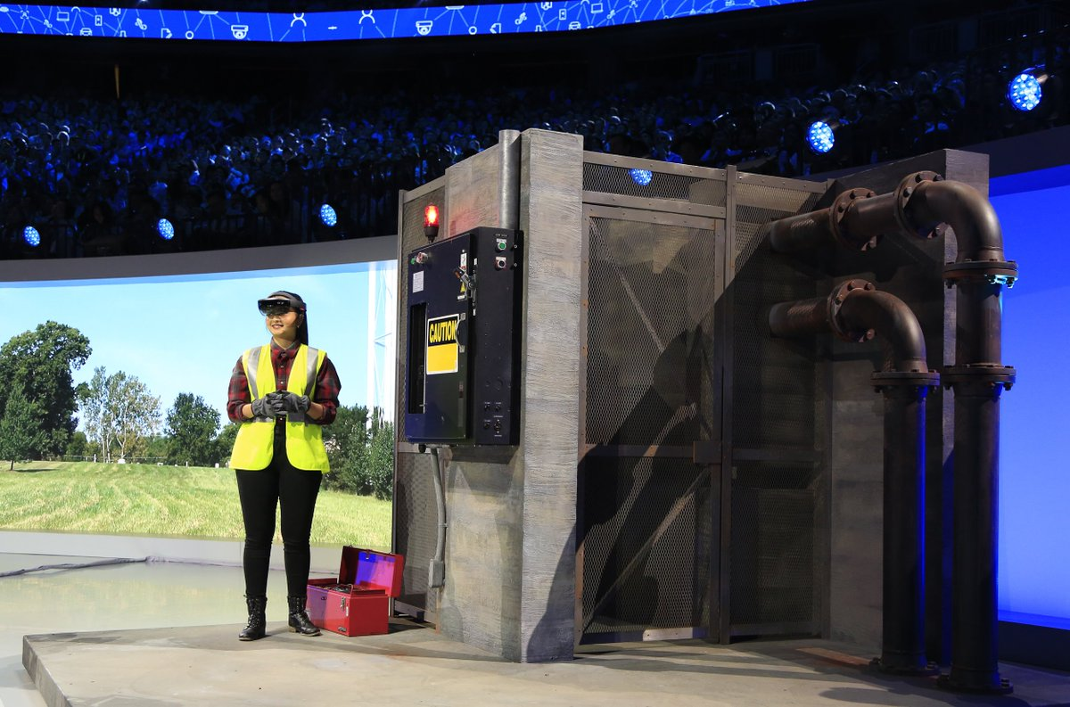 Women in yellow safety vest wearing a HoloLens on stage