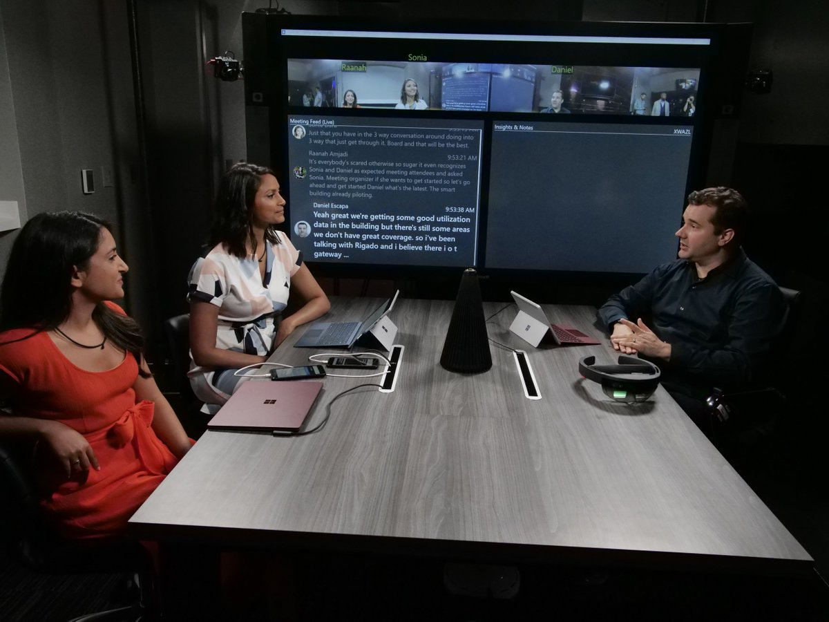 Three people sitting at work table with various technology, including HoloLens