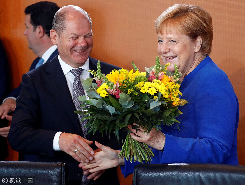 Global times on twitter german chancellor angela merkel receives a german chancellor angela merkel receives a bouquet of flowers for her 64th birthday from finance minister olaf scholz at the weekly cabinet in berlin on izmirmasajfo