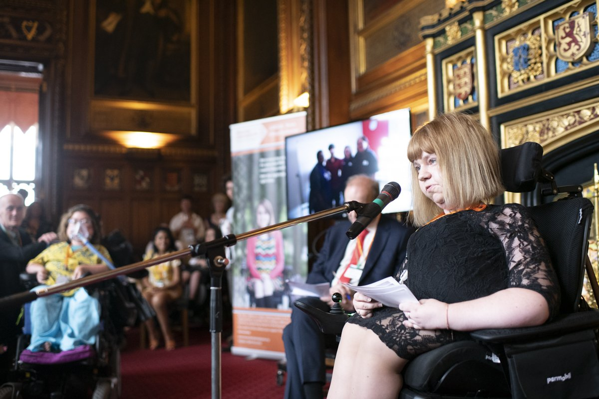 Photo during the celebratory event as Trailblazers Manager, Lauren West takes the mic infront of 40 attending Trailblazers in Speakers House, House of Commons to summarise the last 10 years of campaigning for disability rights and access for young persons with disabilities across the UK. Photo shows Lauren, in her powerchair wearing a smart black dress, blonde hair in a bob, surrounded by many wheelchair users whom are Trailblazers, some Trailblazers can be seen using ventilators due to their muscle-wasting conditions