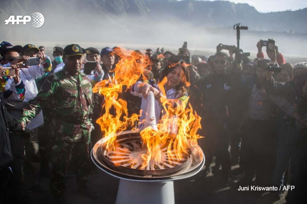 Former Indonesian badminton player Susi Susanti (C) lights the #AsianGames2018 torch at Mount Bromo volcano in Probolinggo, East Java province. The Games will take place in Jakarta and Palembang from August 18 to September 2. by @junipicture