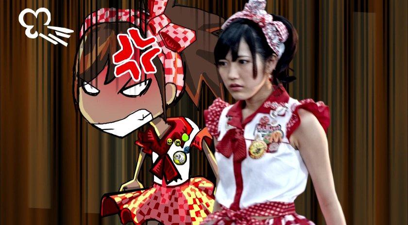 赤いギンガムチェックの衣装を着ている怖い表情の渡辺麻友の画像