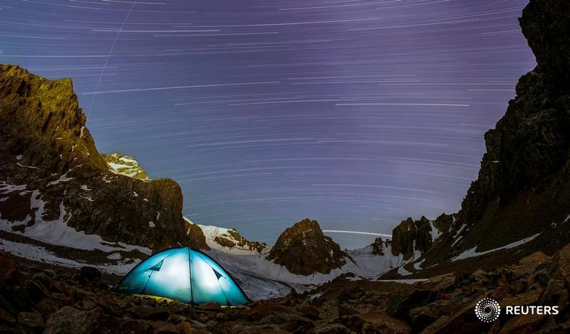 A long exposure picture shows stars and meteor trails above the mountains of Tien Shan in Kazakhstan