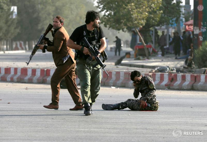 Members of Afghan security forces arrive as an injured man sits on the ground at the site of a blast in Kabul.