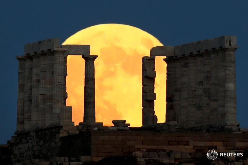 A full moon rises behind the Temple of Poseidon before a lunar eclipse in Greece
