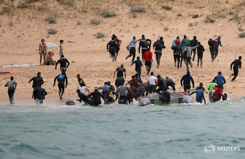Migrants disembark from a dinghy at 'Del Canuelo' beach after they crossed the Strait of Gibraltar from Morocco to Tarifa, Spain