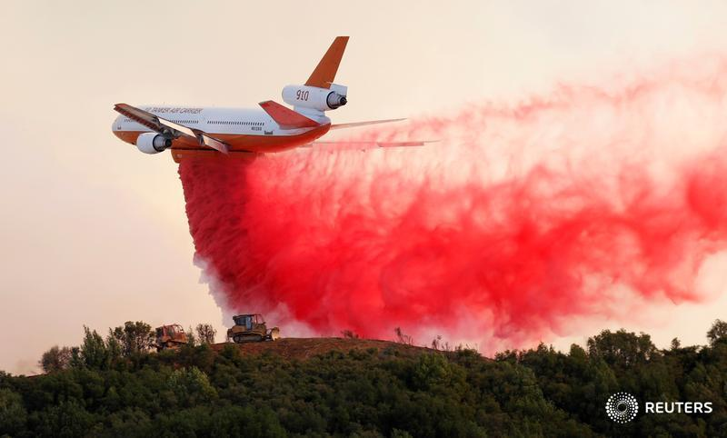 A DC-10 air tanker drops fire retardant along the crest of a hill, as firefighters battle the Mendocino Complex fires in California