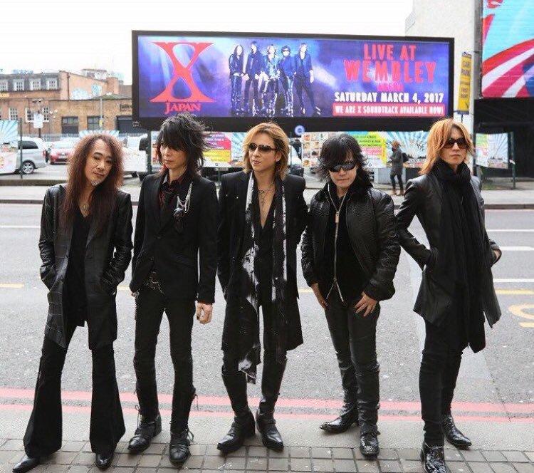 大通りの前に立っている黒い衣装を着たX JAPANの画像
