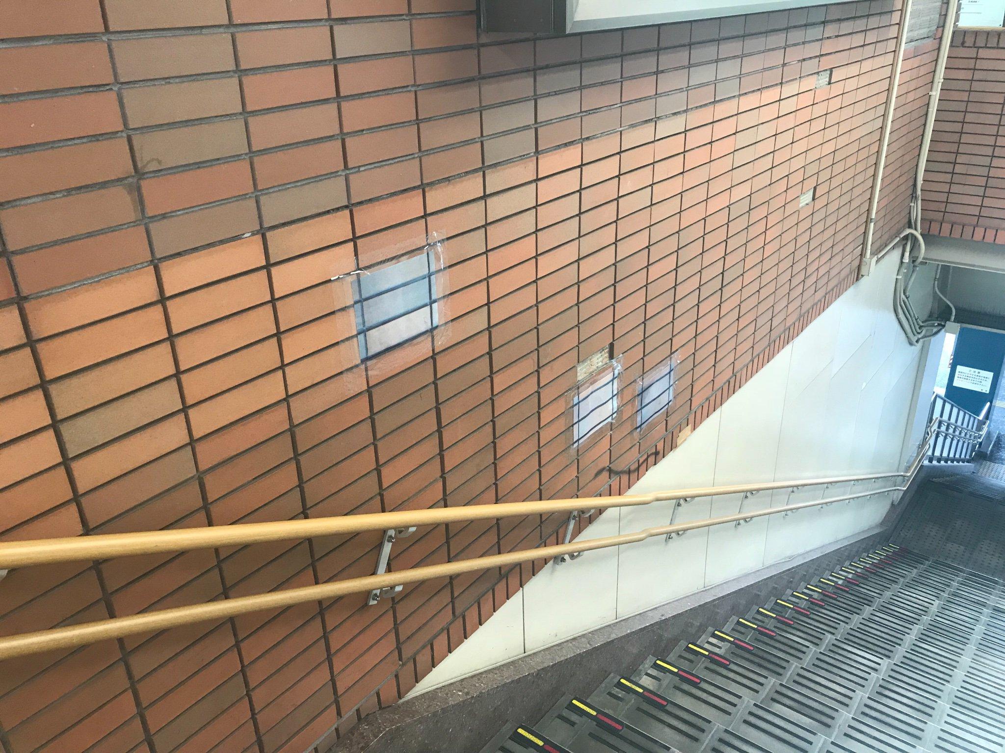 タイルが剥がれたところをタイルが印刷された紙で補修している金沢文庫駅