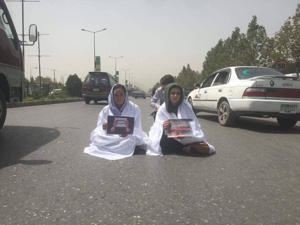 #Kabul - two female protesters, wearing shrouds, sit in the middle of busy Darulaman Road, in Kabul city, protesting against the ongoing situation in #Ghazni