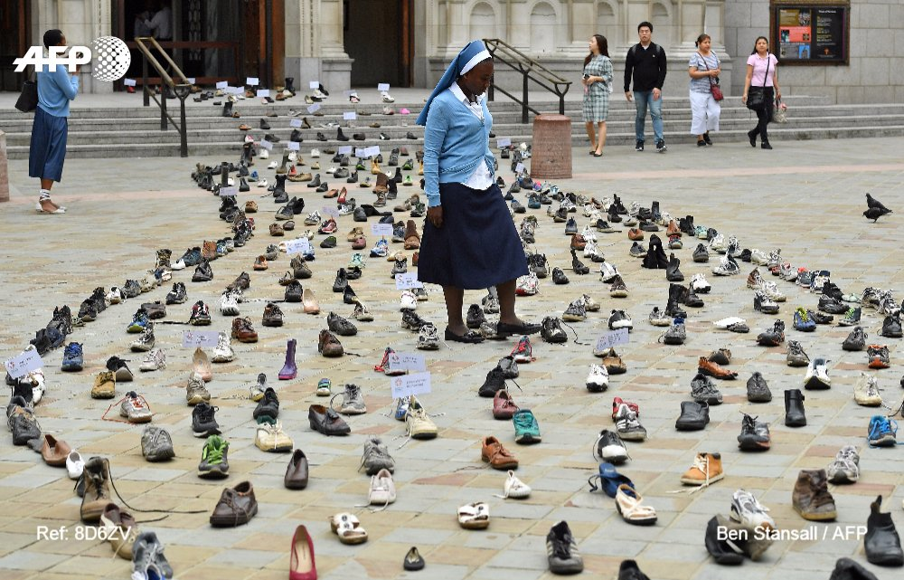 A member of a Catholic agency walks through shoes displayed outside Westminster Cathedral in central London to promote Pope Francis' refugee campaign, which is calling for world leaders to back global agreements aimed at assisting refugees and migrants