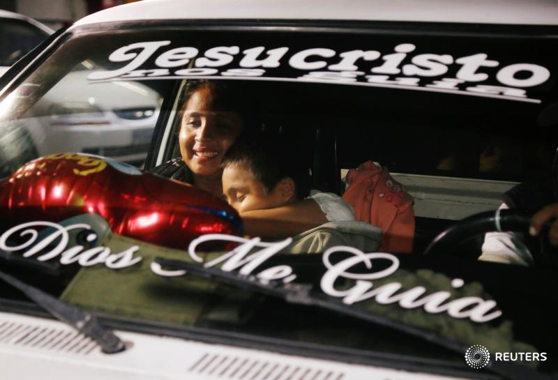 Elsa Ortiz, who had been separated from her son Anthony David Tobar at the U.S. border, holds him after they were reunited in Guatemala. The writing on the windshield reads 'Jesus Christ, God guide me.'