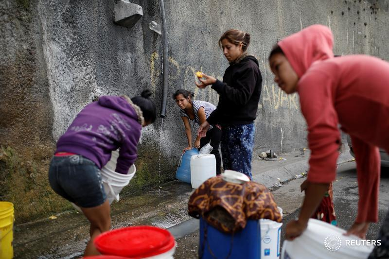 Women fill containers with water coming from a mountain, in a road at Plan de Manzano slum in Caracas, Venezuela
