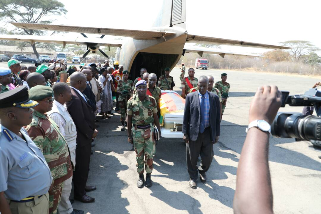 Pallbearers carry the casket bearing the body of the late National Heroine Cde Thokozile Mathuthu in Hwange. Matabeleland North state minister  Cde Cain Mathema consoles late Mathuthu widower Jonathan on arrival in Hwange .-(Pictures by Eliah Saushoma) <br>http://pic.twitter.com/JRQk0Tcmmu