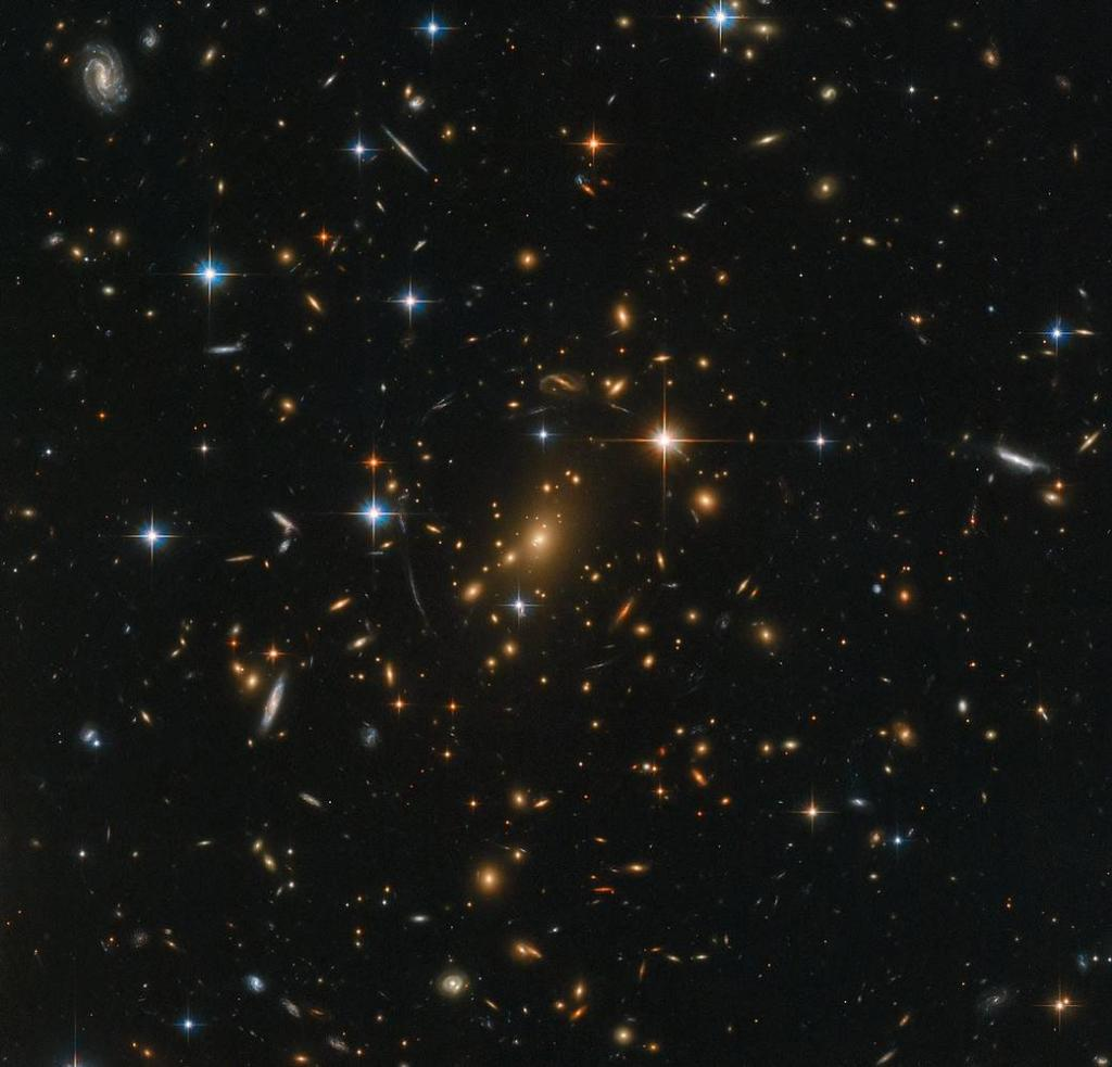 A few stars closer to home shine brightly in the foreground, while a massive galaxy cluster nestles at the very center of the image — an immense collection of maybe thousands of galaxies, all held together by the relentless force of gravity: https://t.co/i7wfbbOTSO