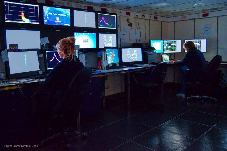 Two women in dark, window less room work in front of several computer screens that are showing graphs and images of the seafloor.