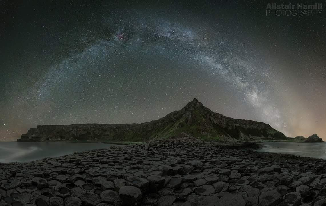 The arc of the Milky Way sweeps above the iconic stone of the Giant's Causeway.