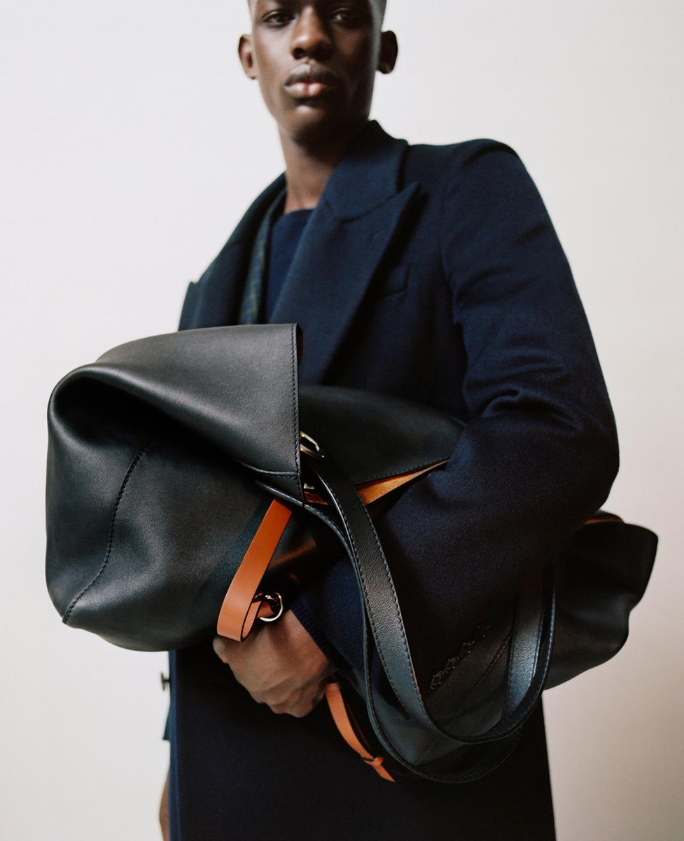 MODERN ELEGANCE   Malick carries the new Grommet Detail Tote and wears a double-breasted wool coat brby.co/75e