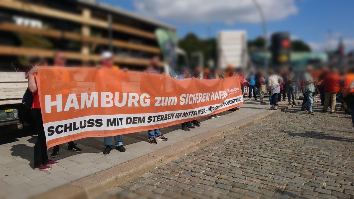 """Das Bild zeigt einen Lauti-Wagen, vor dem mehrere Menschen ein Banner mit der Aufschrift """"Hamburg zum sicheren Hafen - Schluss mit dem Sterben im Mittelmeer - für sichere Fluchtwege"""" halten."""