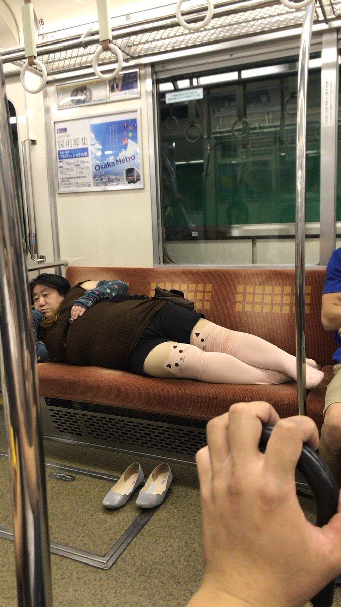 千日前線の電車内で猫の靴下履いたおばさんが寝転んでいる画像