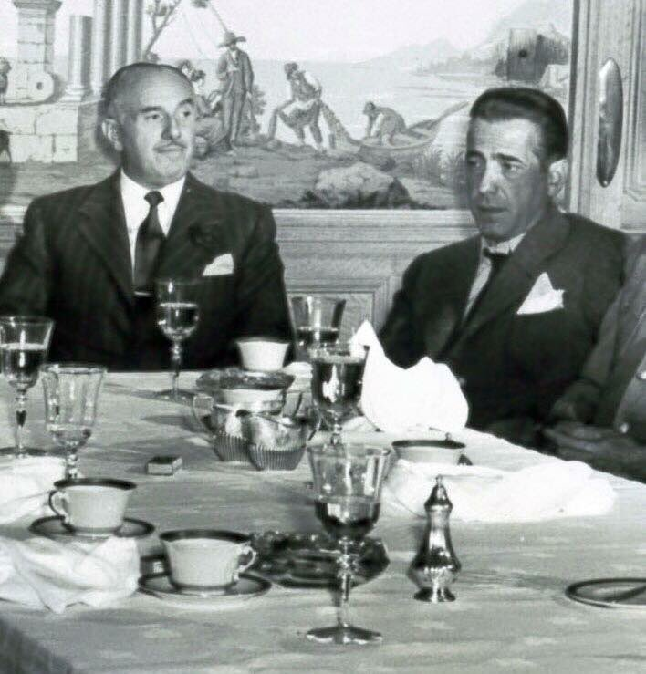 Jack Warner, the legendary founding president and driving force behind the Warner Brothers film studio, passed away on this day in 1978. He is seen here at lunch with Humphrey Bogart. The two men frequently sparred (and exchanged hilarious telegrams) over Bogie's film roles.