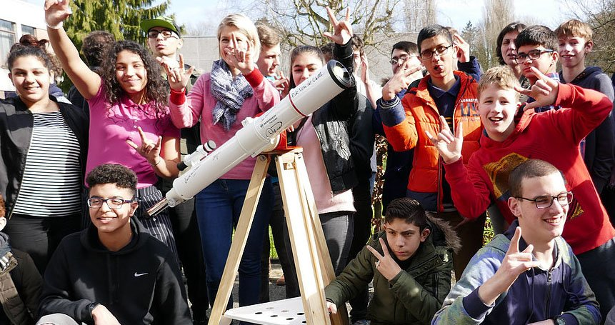 SSVI students gathered around a telescope looking excited.