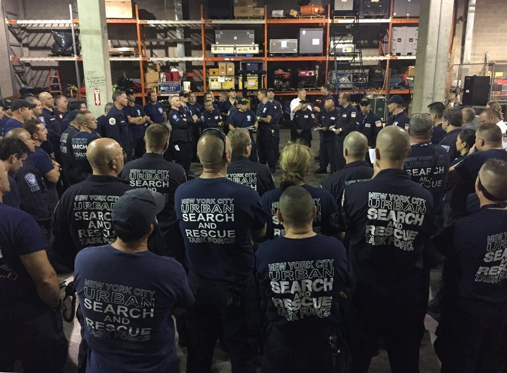 A large group of New York City Urban Search and Rescue team members stand in a warehouse. In the backgound, you see large shelves with equipment package in boxes.