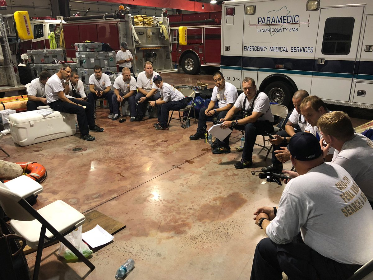 A large group of men sit in a semi-circle in a garage that has paramedic trucks and fire trucks in the background. They are all wearing gray shirts that say Ohio TF-1 on the back.