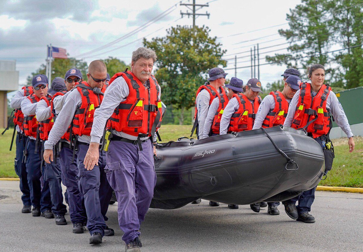 Men and women carry rescue boat. They all wear safety life vests. American flag flys in background