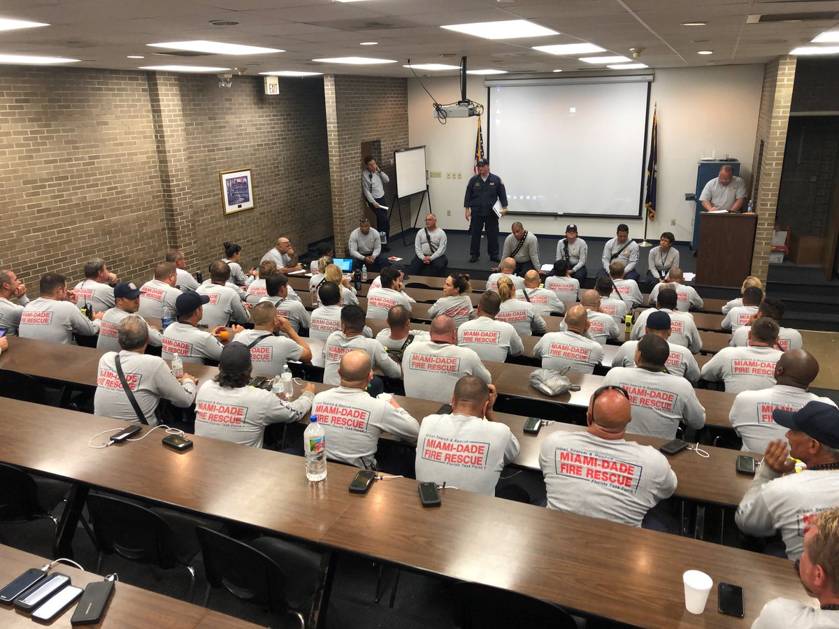 Classroom filled with people wearing shirts with  Miami dade fire rescue written on back