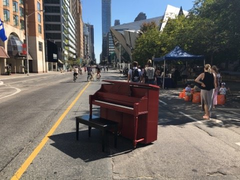 The big red piano is waiting for you! Head to @the_rcm this #OpenStreetsTO for a chance to play in the streets. Photo