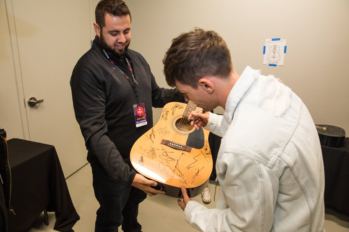 .@Louis_Tomlinson signing guitars backstage at the 2017 #iHeartFestival 🎸