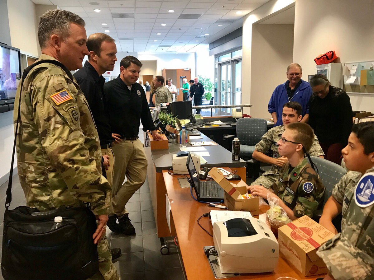 Three young cadets with the North Carolina Civil Air Patrol sit behind a desk that has computers and lunch boxes. They are talking to two FEMA staff members including Administrator Long, along with a man in military uniform.