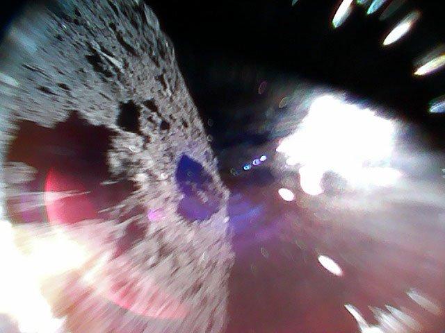 このダイナミックな写真は、2018年9月22日、11:44(日本時間)頃にRover-1Aが撮影したものです。リュウグウ表面において移動中(ホップ中)に撮影されました。左側半分がリュウグウの表面で、右側の白い部分は太陽光によるものです。 (はやぶさ2プロジェクト)