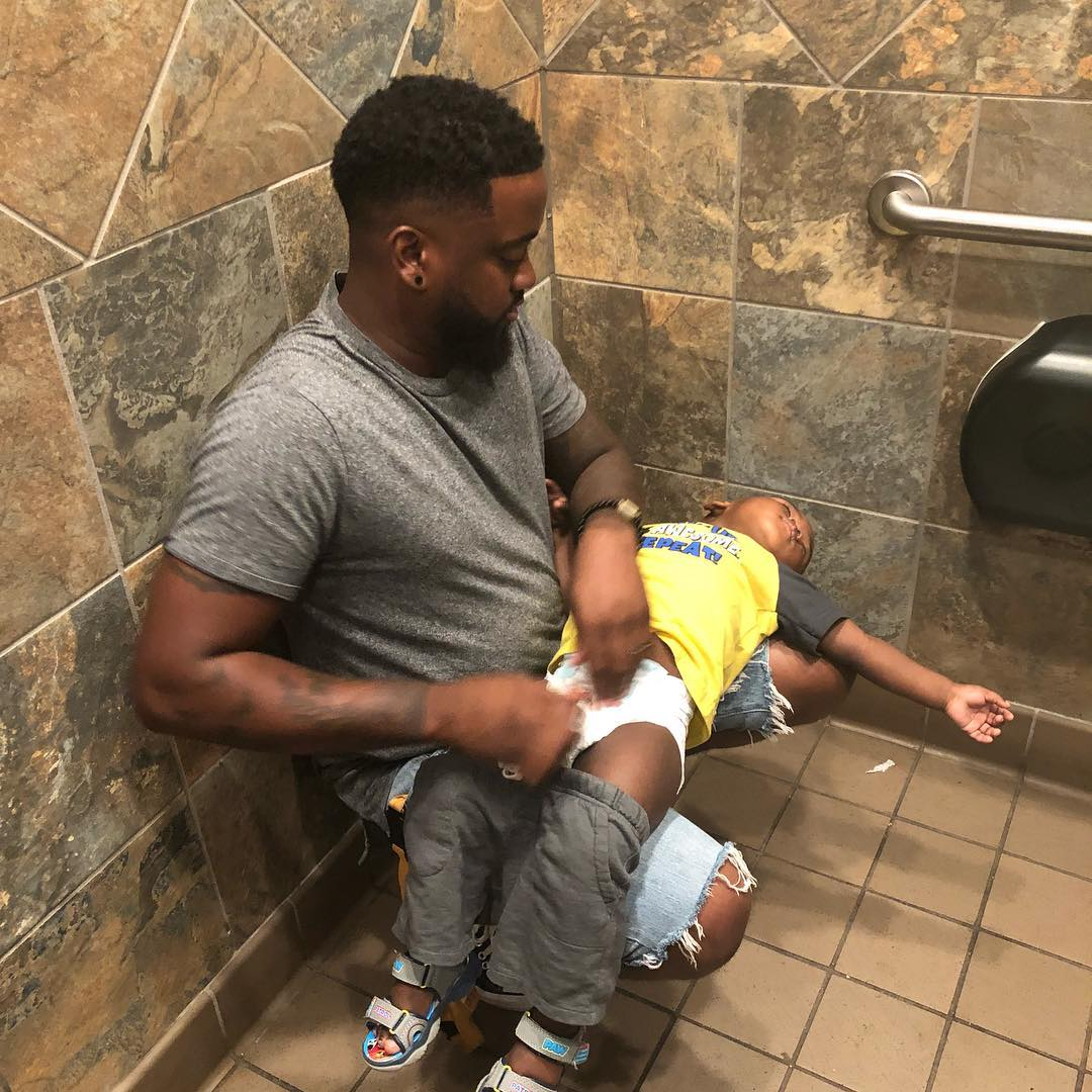 This dad, Donte Palmer, is calling for Changing Tables In Men's  Rest Rooms. I'm with him.  He is balancing against the wall while his son is stretched out on his knees.   RETWEET THIS!