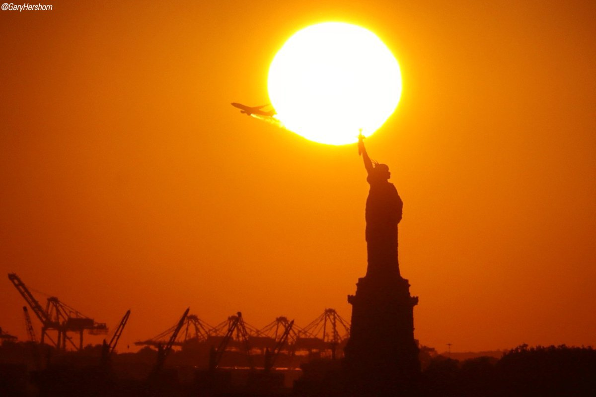 A brilliant sun set behind the Statue of Liberty on Thursday as a plane passed by. (via @GaryHershorn) https://t.co/SxSa4PNY9w