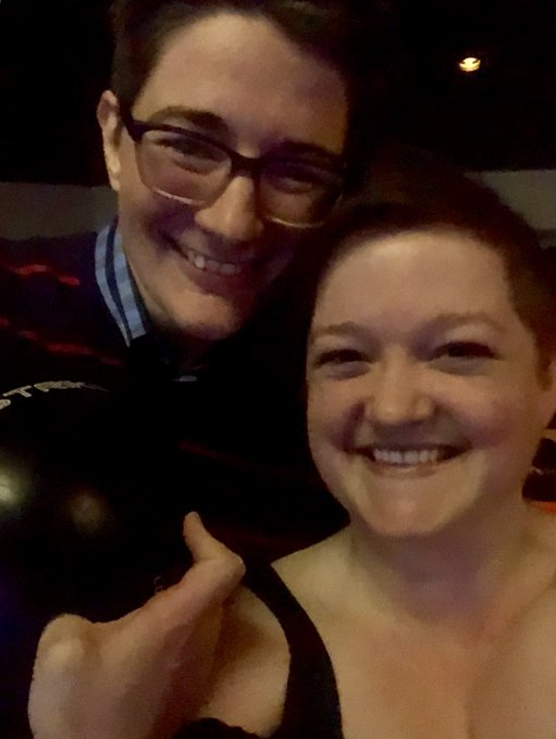 Two women smiling. Both have light skin and short dark hair. One woman (Charlie) has glasses and is holding a bowling ball in her hand.