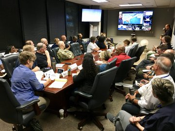 A packed conference room full of FEMA staffers and military partners participating on a conference call.