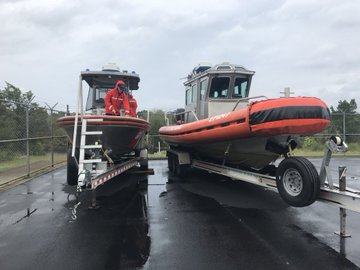 Two US Coast Guard boats are in a rainy parking lot, with two men working on them.