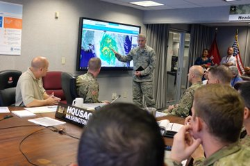 A conference room with US Army Corps of Engineer staffers participating in a meeting about Hurricane Michael. The storm is shown on a radar photo on a big screen and one of the staffers is pointing to it.