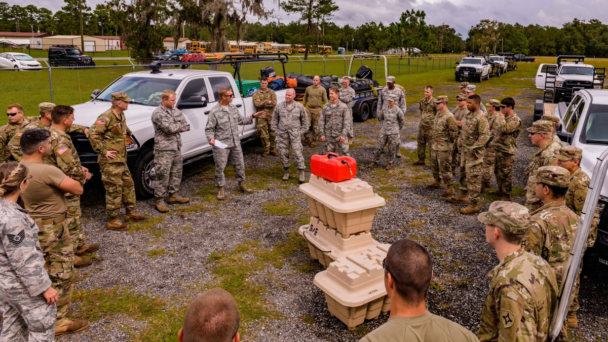 A large group of soldiers with the National Guard are positioned in a large circle in a gravel parking lot. In the middle is a stack of heavy duty equipment in cases.