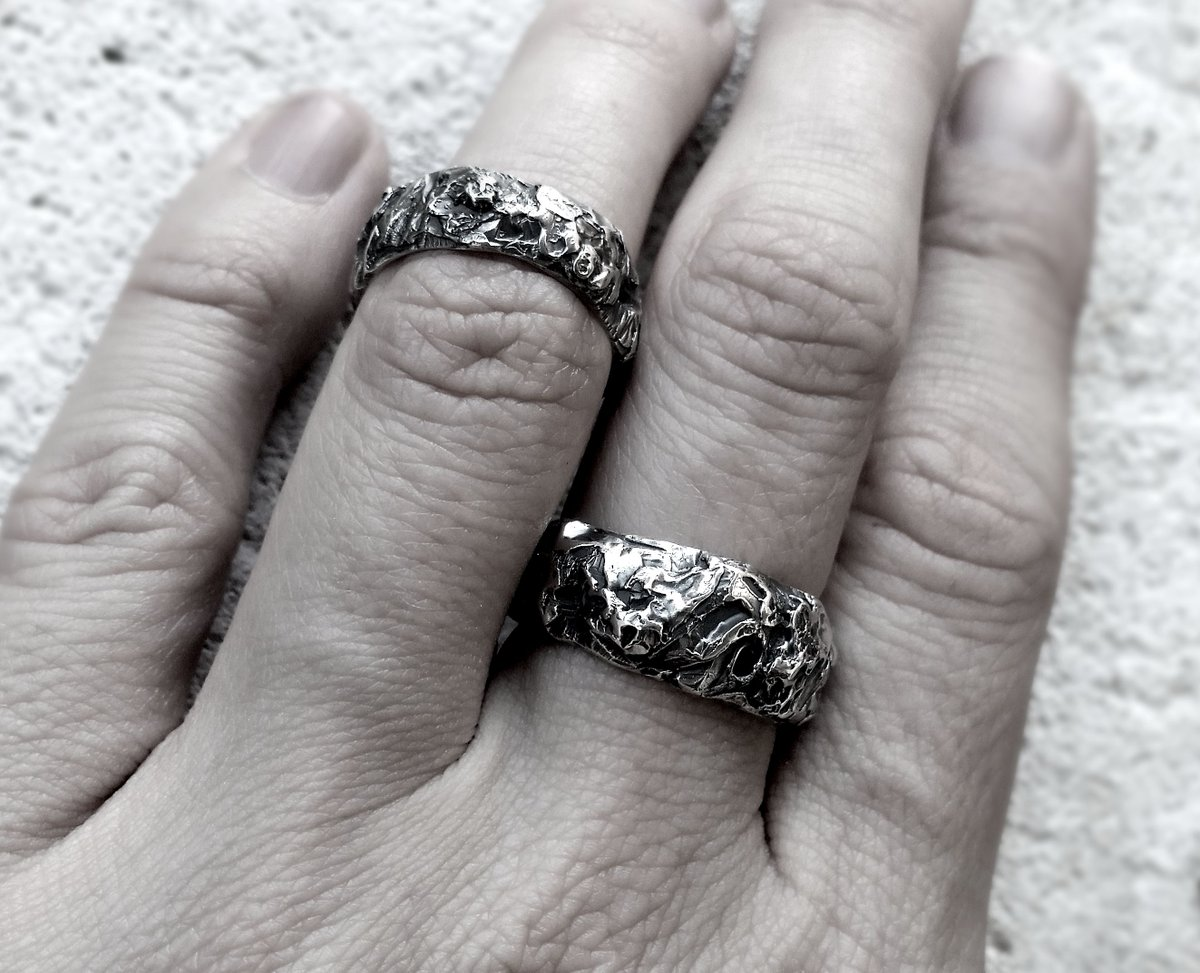 two textured sterling silver rings on a hand