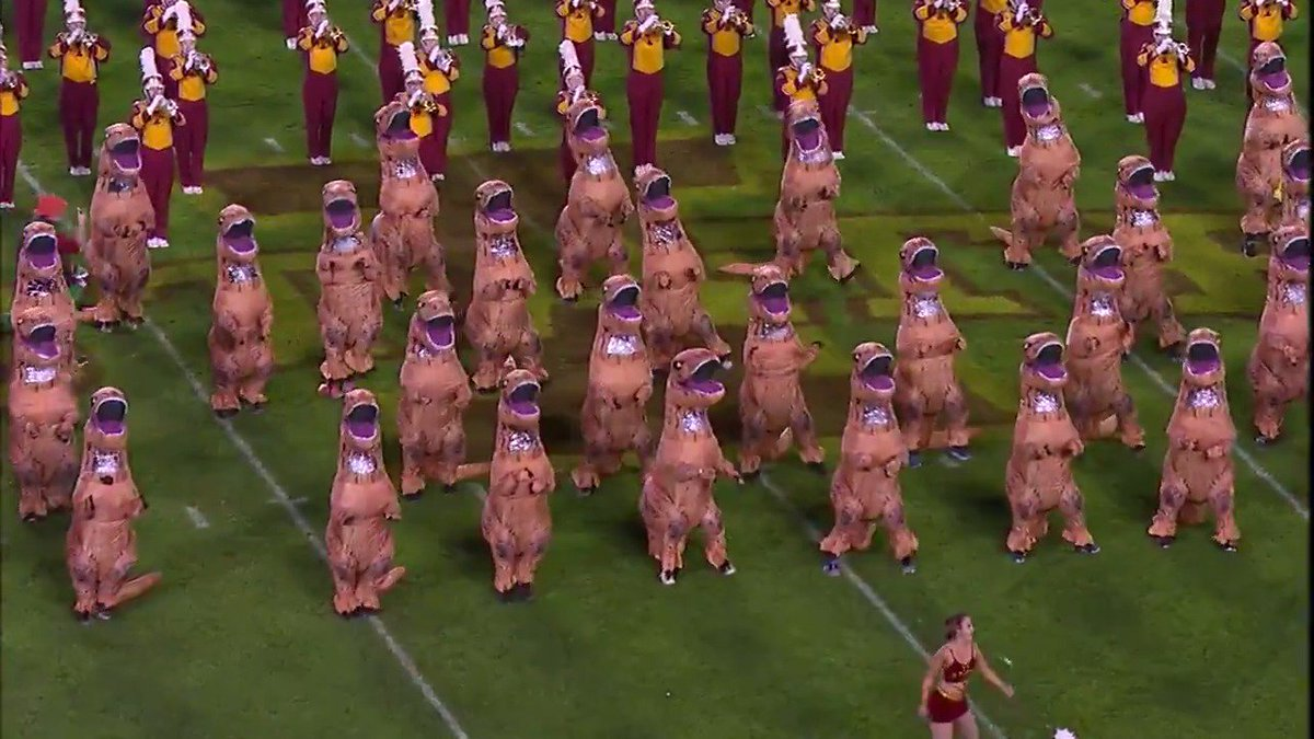 Dinosaur suits bring majesty to halftime performance of 'Jurassic Park' theme