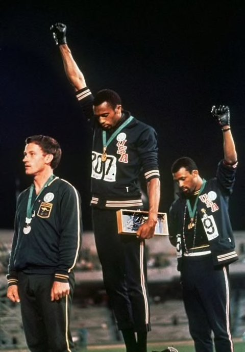"""""""Then the three athletes turned to the right, to face the flags. The Star-Spangled Banner began. Smith bowed his head as if in prayer and freed his young face of expression. Then he tensed the muscles of his right shoulder and began the irrevocable lifting of his fist."""""""