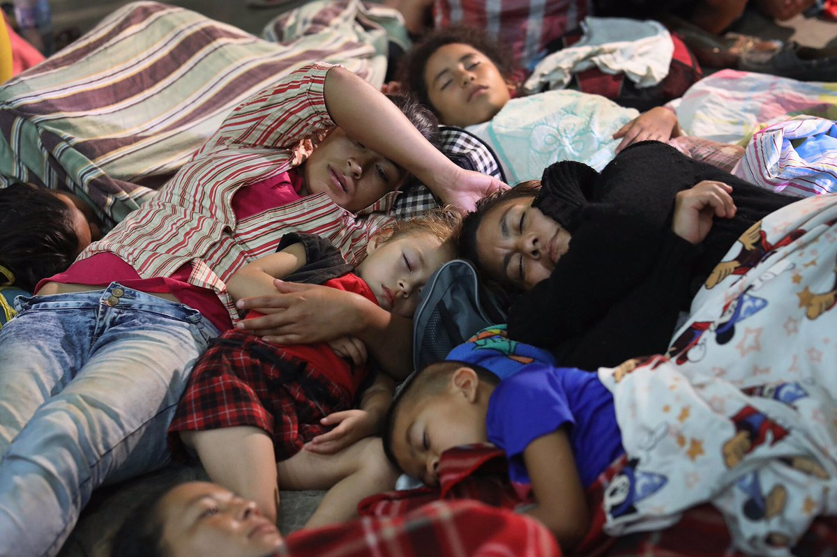 Central American families, part of a caravan of as many as 2,000 migrants, bed down for the night at a community gym in southeastern Guatemala. Trump has threatened to withhold aid from Central American countries that don't stop them. #gettyimages #gettyimagesnews #caravana